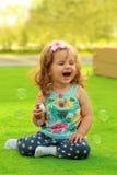 Muchacha de un año de risa que aprende soplar burbujas de jabón y que se sienta en el césped iluminado por el sol Imagen de archivo libre de regalías