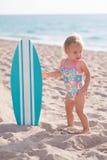 Muchacha de un año en la playa con la tabla hawaiana Imagen de archivo libre de regalías