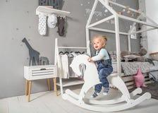 Muchacha de un año que juega cerca en el cuarto con un caballo del juguete, ska Imagen de archivo