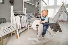 Muchacha de un año que juega cerca en el cuarto con un caballo del juguete, ska Fotos de archivo libres de regalías