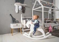 Muchacha de un año que juega cerca en el cuarto con un caballo del juguete, ska Fotografía de archivo