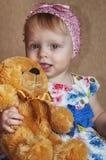 Muchacha de un a?o feliz que juega y que presenta con un oso de peluche fotos de archivo libres de regalías