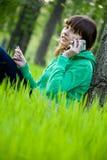 Muchacha de universidad bastante joven que usa el teléfono celular Imagen de archivo