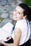 Muchacha de universidad feliz que estudia al aire libre Imagen de archivo