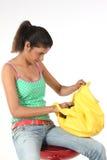 Muchacha de universidad que busca en su bolso amarillo Imágenes de archivo libres de regalías