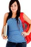 Estudiante universitaria que presenta con el bolso y los libros