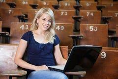 Muchacha de universidad que usa la computadora portátil Imágenes de archivo libres de regalías