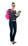 Muchacha de universidad sonriente que usa la PC de la tablilla Foto de archivo libre de regalías