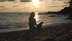 Muchacha de vacaciones que se sienta en la playa en la puesta del sol almacen de metraje de vídeo