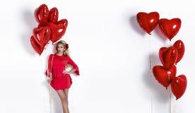 Muchacha de Valentine Beauty con el balón de aire rojo aislado en el fondo blanco Mujer joven feliz hermosa que presenta producto imagen de archivo libre de regalías