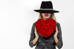 Muchacha de Valentine Beauty con las rosas rojas del corazón Retrato de un modelo femenino joven con el regalo y el sombrero, ais imágenes de archivo libres de regalías