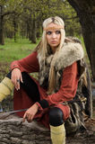 Muchacha de Vikingo con la espada en una madera Imagen de archivo