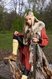 Muchacha de Vikingo con la espada en una madera imagenes de archivo