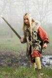 Muchacha de Vikingo con la espada en una madera de la niebla fotografía de archivo libre de regalías