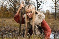 Muchacha de Vikingo con la espada en una madera de la niebla Fotos de archivo libres de regalías