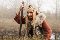 Muchacha de Vikingo con la espada en una niebla Fotos de archivo libres de regalías