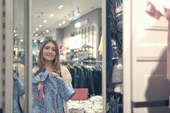 Muchacha de Yong que elige la ropa y que mira para duplicar en tienda de la alameda o de ropa Imágenes de archivo libres de regalías