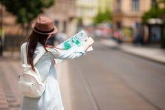 Muchacha de Youn con el citymap que camina en las calles europeas Mujer caucásica del viaje con el mapa afuera durante días de fi Imagen de archivo libre de regalías