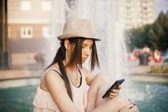 Muchacha de Youn con el teléfono elegante Foto de archivo libre de regalías