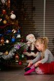 Muchacha debajo de agujas de la limpieza del árbol de navidad Foto de archivo