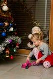 Muchacha debajo de agujas de la limpieza del árbol de navidad Fotografía de archivo