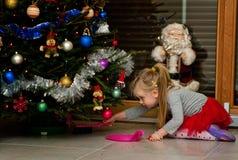 Muchacha debajo de agujas de la limpieza del árbol de navidad Fotos de archivo libres de regalías
