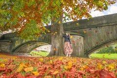 Muchacha debajo de un árbol con las hojas que caen Imagen de archivo libre de regalías
