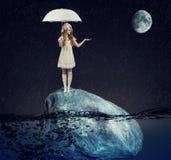 muchacha debajo de un paraguas blanco en una roca grande fotografía de archivo libre de regalías