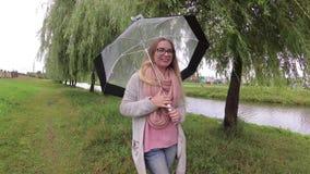 Muchacha debajo de un paraguas en mún tiempo almacen de metraje de vídeo