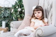 Muchacha decepcionada tranquila que se sienta en una silla fotografía de archivo