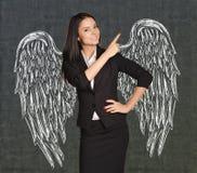 Muchacha del ángel con las alas pintadas en la pared Fotos de archivo