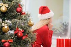 Muchacha del árbol de navidad en el sombrero de santa cerca de la ventana Fotografía de archivo libre de regalías