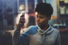 Muchacha del ébano que toma la imagen en el teléfono móvil en la noche Fotografía de archivo libre de regalías