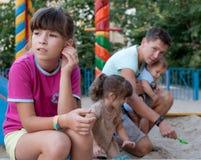 Muchacha del adolescente celosa de su hermana y hermano más jovenes Foto de archivo libre de regalías
