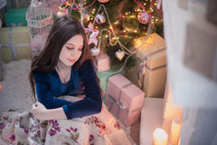 Muchacha del adolescente cerca de la mirada de la chimenea en la vela ardiente Foto de archivo libre de regalías