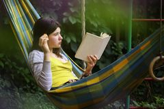 Muchacha del adolescente con el albaricoque del libro en foto al aire libre de la hamaca Imagen de archivo libre de regalías