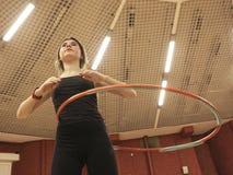 Muchacha del adolescente con el aro del hula en gimnasio Fotografía de archivo