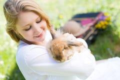 Muchacha del adolescente con el conejito en la naturaleza Imagenes de archivo