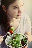 Muchacha del adolescente con el cuenco de ensalada cortado del tomate del pepino Fotos de archivo libres de regalías