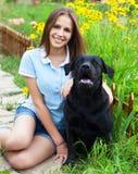 Muchacha del adolescente con el labrador retriever negro Fotografía de archivo libre de regalías