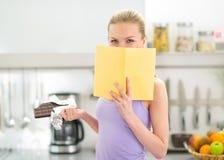 Muchacha del adolescente con el libro de lectura del chocolate Foto de archivo