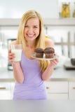 Muchacha del adolescente con el mollete y la leche en cocina Imagenes de archivo