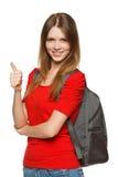 Muchacha del adolescente con el morral que muestra el pulgar para arriba Imagen de archivo libre de regalías