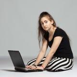 Muchacha del adolescente con el ordenador portátil Imágenes de archivo libres de regalías