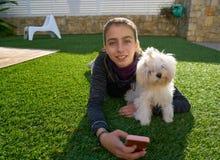 Muchacha del adolescente con el teléfono móvil y el perrito Imagenes de archivo