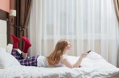 Muchacha del adolescente con el telecontrol de la TV Imágenes de archivo libres de regalías