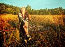 Muchacha del adolescente con la bicicleta en prado del verano Foto de archivo