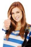 Muchacha del adolescente con la mochila y el pulgar de la escuela para arriba Foto de archivo