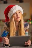 Muchacha del adolescente con la tarjeta de crédito usando la PC de la tableta Imágenes de archivo libres de regalías