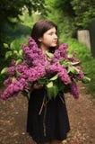Muchacha del adolescente con las flores de la violeta de la lila Imagen de archivo